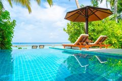 beach chair with swimming pool and sea beach background in Maldives